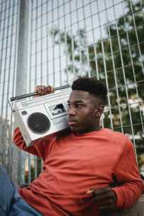 wistful black man listening to radio from vintage tape recorder