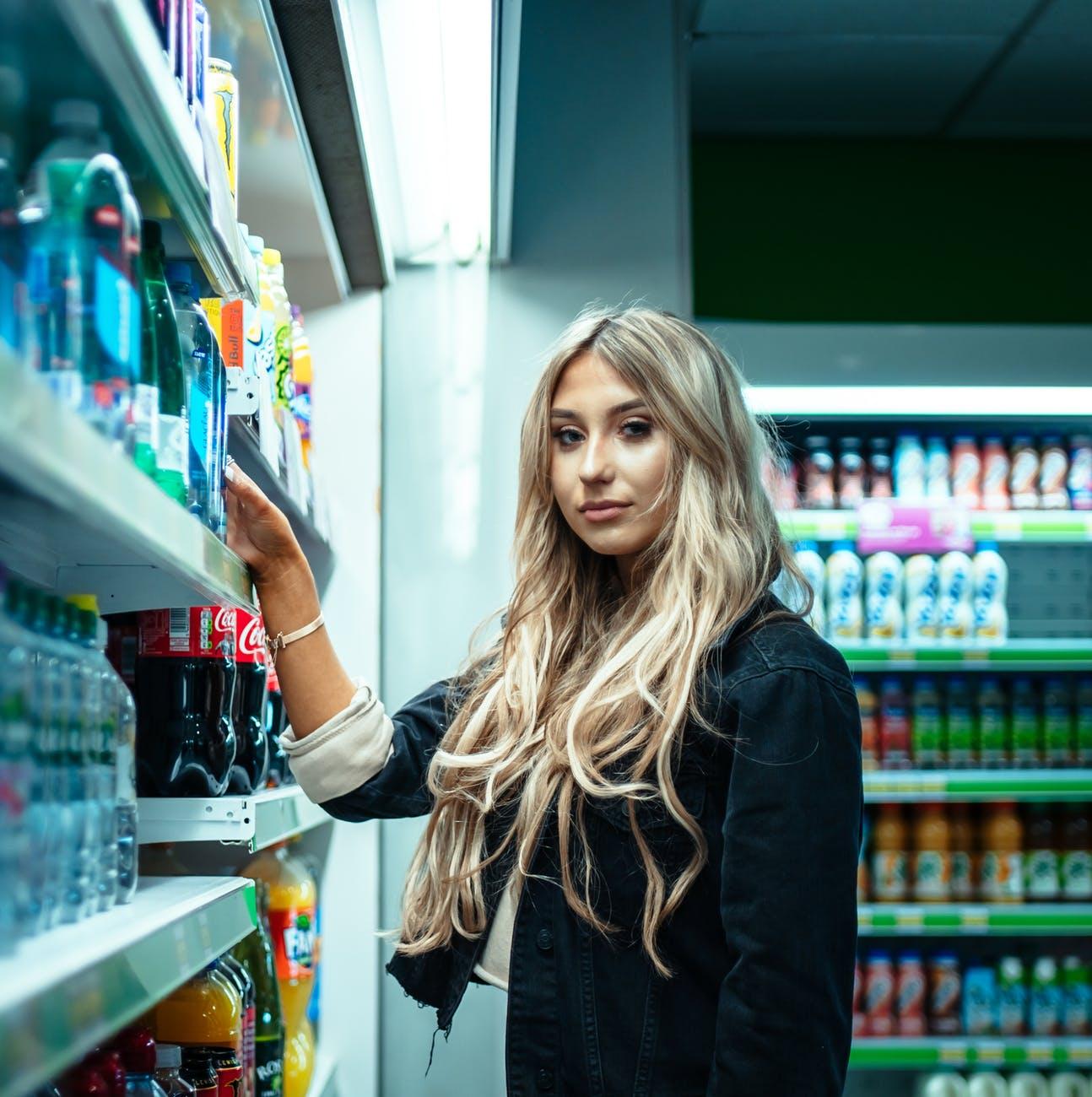 woman standing beside store shelf