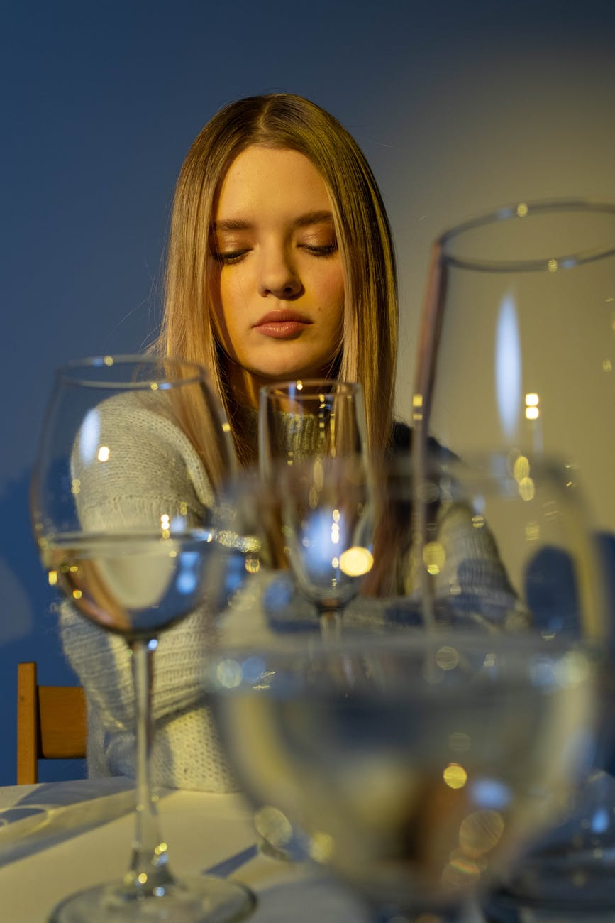 woman in gray long sleeve shirt looking at the wine glass