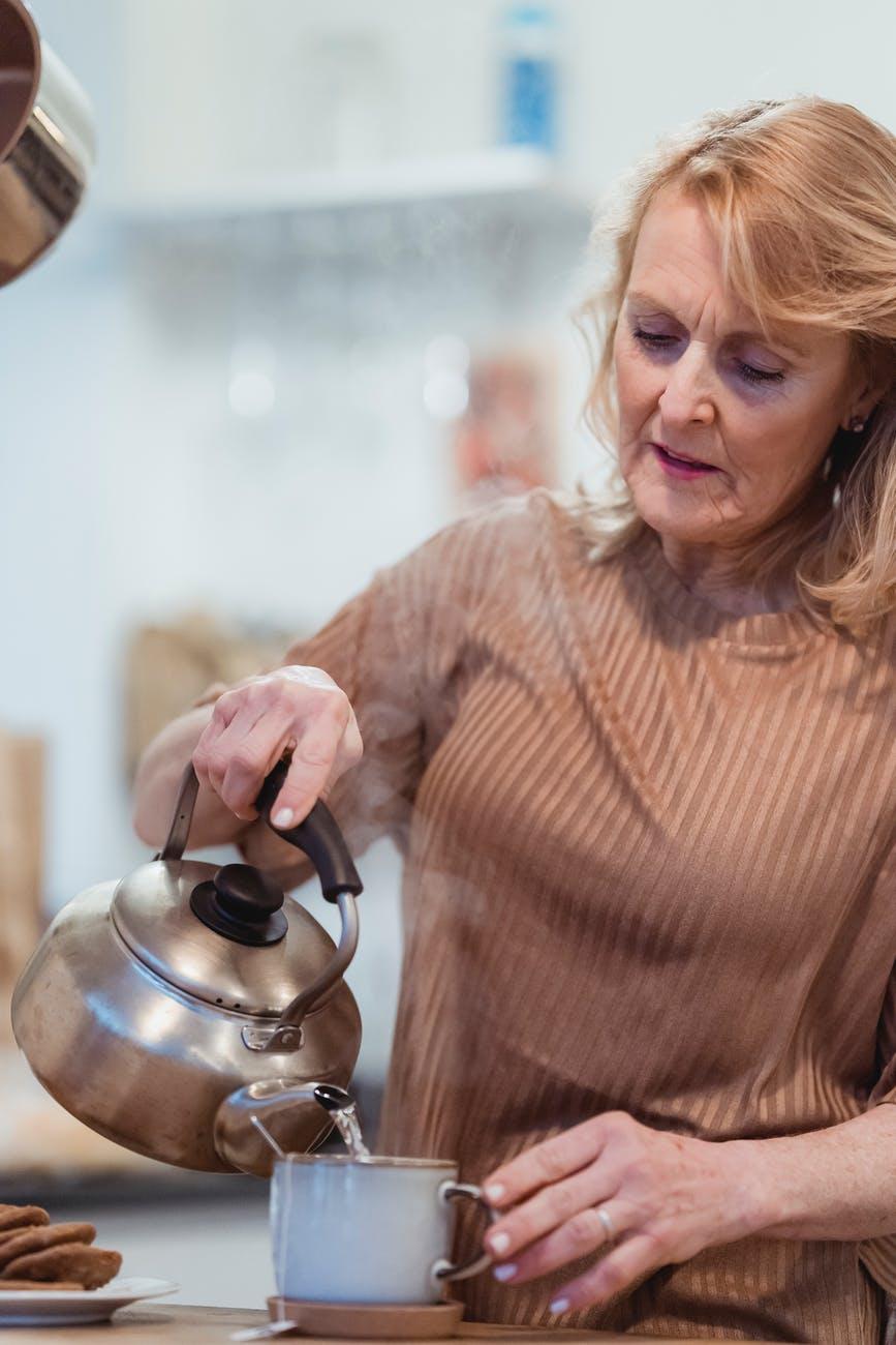 elderly woman preparing tea in house kitchen