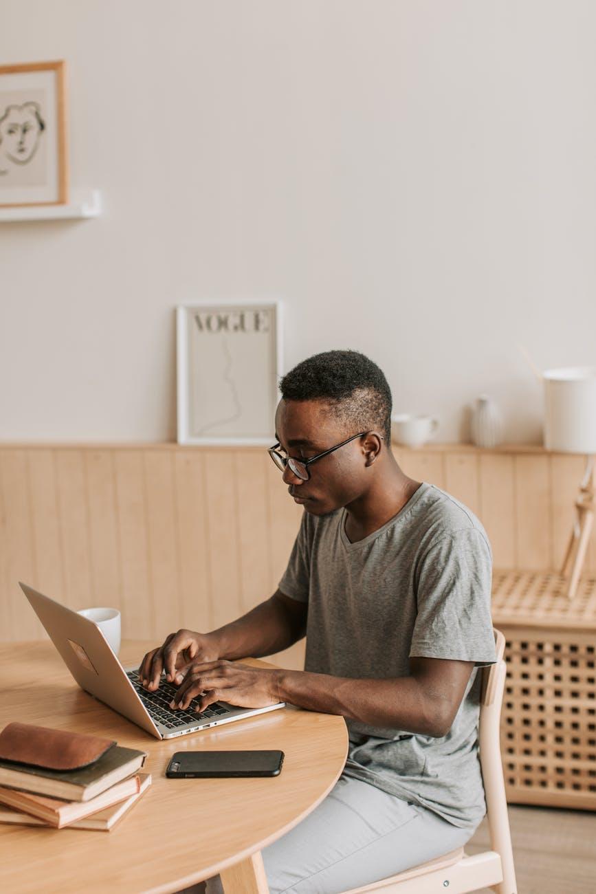 man in gray t shirt typing on laptop