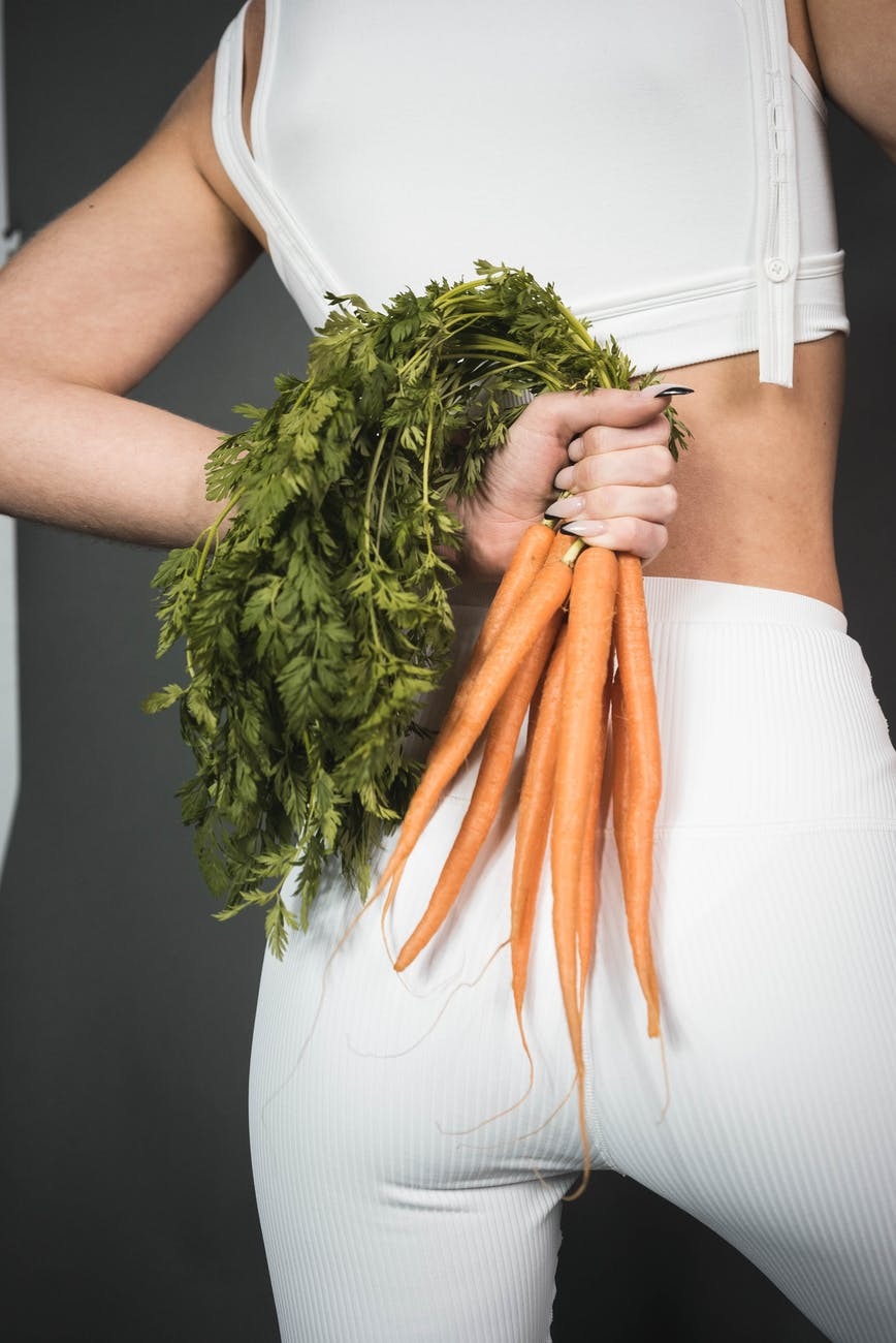 woman in white leggings holding green and orange plant